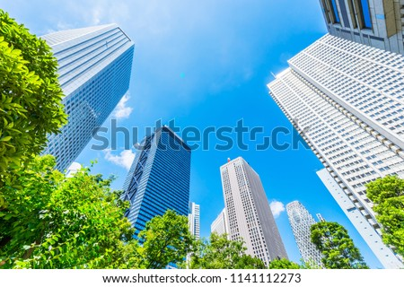 Asia Business concept for real estate, corporate construction and ecology - looking up view of panoramic modern city skyline with blue sky and green tree in shinjuku, tokyo, japan #1141112273