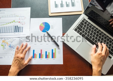 Asia business woman analyzing investment charts on desk.Vintage tone,Retro filter effect,Soft focus,Low light.(selective focus)