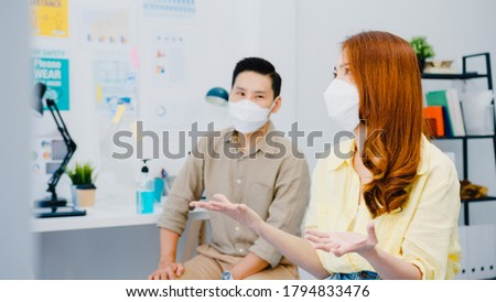 Asia businesspeople meeting brainstorming ideas conducting business presentation ideas project colleagues and wear protective face mask back in new normal office. Lifestyle and work after coronavirus.
