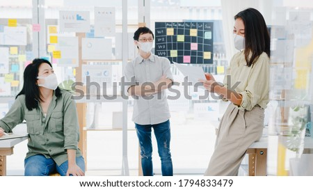 Asia businesspeople meeting brainstorming ideas conducting business presentation ideas project colleagues and wear protective face mask back in new normal office. Lifestyle and work after corona virus
