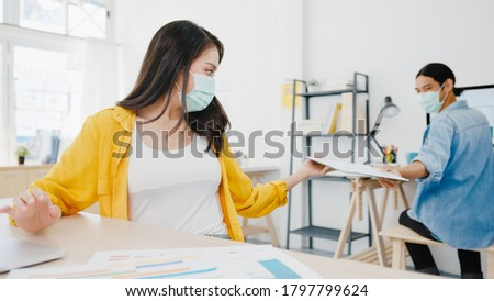 Asia businesspeople wear face mask for social distancing in new normal situation for virus prevention and passing documents with keeping a distance in office. Lifestyle and work after corona virus.
