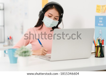 Asia businesswoman social distancing in new normal situation for virus prevention while using laptop presentation to colleagues about plan in video call while work in office. Life after corona virus.