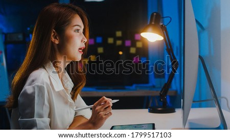 Asia businesswoman using computer talk to colleagues about plan in video call while working from home at living room at night. Self-isolation, social distancing, quarantine for coronavirus prevention.
