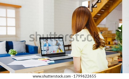 Asia businesswoman using laptop talk to colleagues about plan in video call meeting while working from home at living room. Self-isolation, social distancing, quarantine for corona virus prevention.