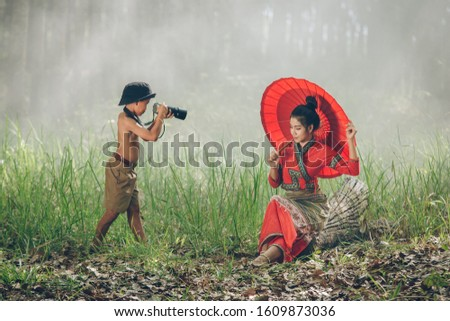 Asia children taking a picture for a beautiful woman at countryside,Rural concept,Boy takes pictures of his girl outdoors.