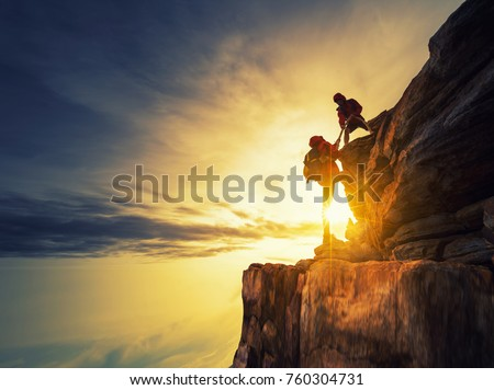 Asia couple hiking help each other silhouette in mountains with sunlight.