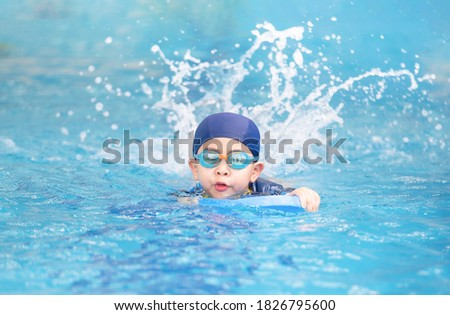 Asia cute boy wearing swimming suit and goggles used foam to practice swimming in swimming pool. Healthy kid enjoying active lifestyle. Refreshing and relax to exercise on summer holiday
