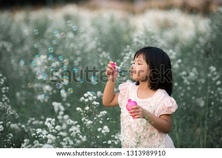 Asia Cute girl plays soap bubbles in a flower garden. #1313989910