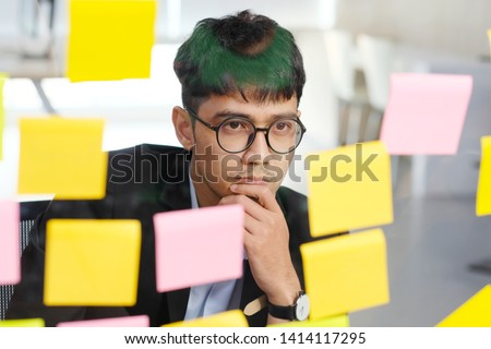 Asia entrepreneur, Young asian businessman thinking while reading sticky notes at office, business brainstorming creative planing ideas to success in business concept