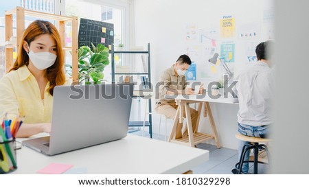 Asia female wear face mask for social distancing in new normal situation for virus prevention while using laptop and separated by acrylic partition stand in office. Life and work after corona virus.