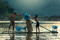 Asia,Fisherman and son on the raft in mekong river Thai -Laos.