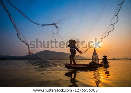 Asia fisherman net using on wooden boat casting net sunset or sunrise in the Mekong river - Silhouette fisherman boat with mountain background life person countryside  #1276536985
