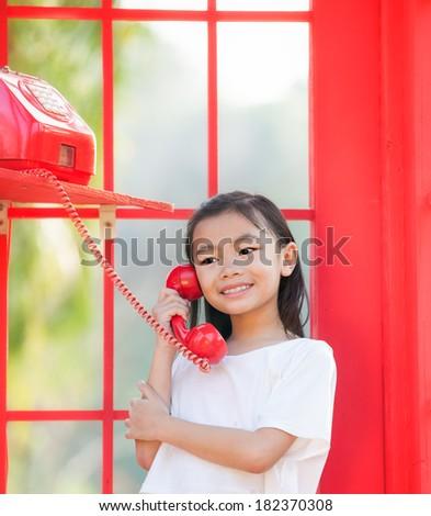 asia girl calling in red in a public phone
