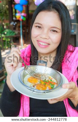 Asia girl eat Egg pan in restaurant.