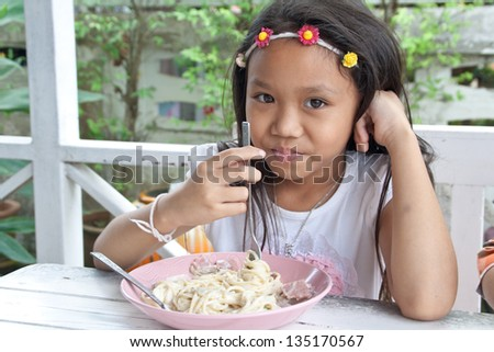 Asia girl  eating spaghetti cream with a fork.