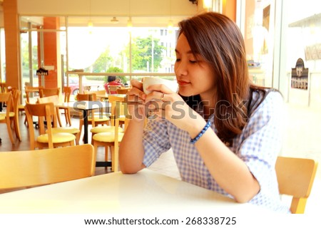 asia girl hold cup of coffee in hand look in window