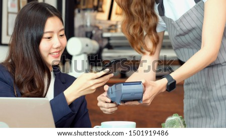 Asia girl make digital payment, Young asian woman holding smart phone for paying contactless at coffee shop, cafe background, Small business financial and contactless payment concept