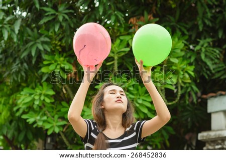 asia girl play color balloon at nature outdoor