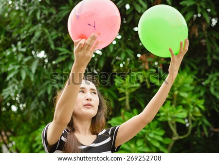 asia girl play color balloon at outdoor background