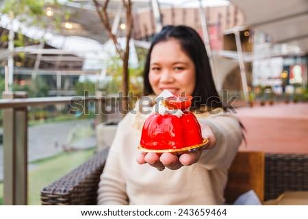 Asia girl sit sofa in restaurat show strawberry cake.