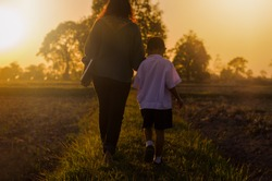 Asia lifestyle rural Family concept of love parent ties mom with children hold one's hand on roads in rural village landscape field and grass sunrise view of countryside go home after school