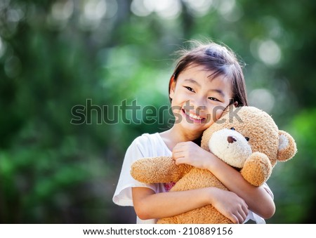 Stock Photo Asia little girl with doll bear in nature park