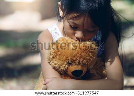 Stock Photo Asia Lovely girl sad mood Hug teddy bear at under the big tree
