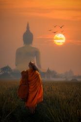 Asia Monk walking behind Big Buddha at Wat Muang Angthong, temple thailand in sunset.