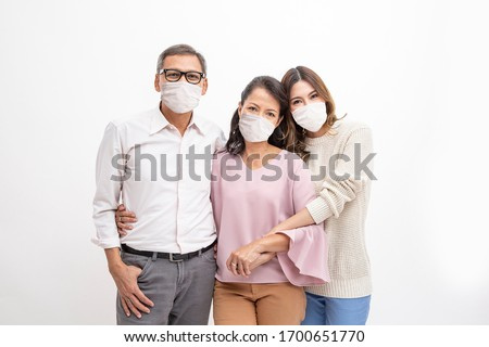 Asia old man and Asia old woman  happy couple standing and hugging and wearing hygienic mask prevent corona virus with daughter on white background.