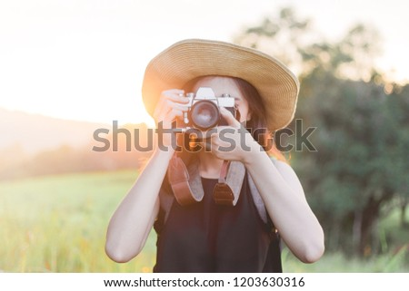 Asia woman outdoor summer smiling lifestyle portrait of pretty young woman having fun in the nature in Thailand in evening with camera travel photo of photographer Making pictures in hipster style hat