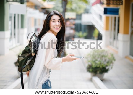 Asia woman walking and using a smart phone in the street in a sunny summer day #628684601