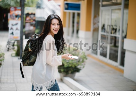 Asia woman walking and using a smart phone in the street in a sunny summer day #658899184