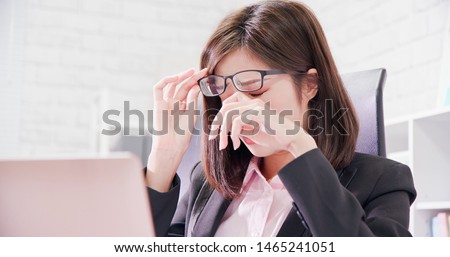 Asia woman worker feel tired and rubbing eyes