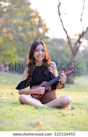 Asia women playing Ukulele in park outdoor