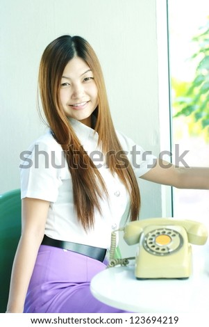 asia women sit with telephone