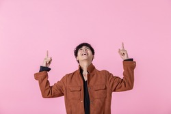 Asian a man handsome young pointing with two hands and fingers to the side eyes looking at camera in love isolated on pink blank copy space studio background.