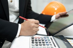 Asian accountant working and analyzing financial reports project accounting with chart graph and calculator in modern office,finance and business concept.