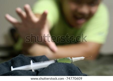Asian addict reaching for green syringe