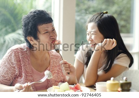 Asian adult daughter feeding fruit to senior mother