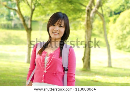 Asian adult student standing outdoor park, green tree background