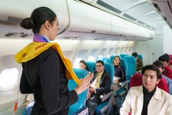 Asian Air hostess staff airline demonstrate safety procedures to passengers prior to flight take off in cabin airplane.