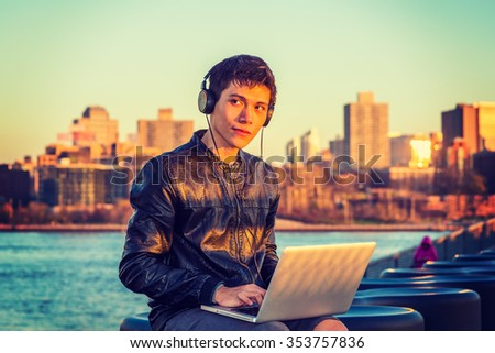 Asian American college student traveling, studying in New York, wearing black leather jacket, headphone, sitting by river in sunset, listening music, working on laptop computer. Instagram effect.
