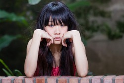 Asian American woman looks sad and forlorn