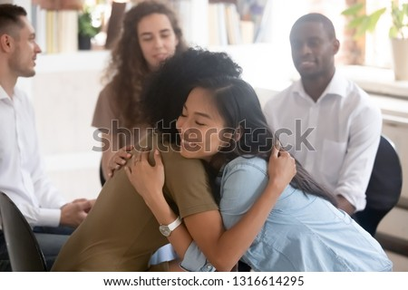 Asian and african women embracing giving psychological support during group therapy counseling session, diverse ladies hug sit in circle feel relief empathy helping friend at with problems addiction