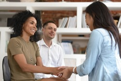 Asian and african women holding hands during group therapy session, diverse friends feeling reconciled relief smiling giving psychological support empathy overcome problem at psychotherapy counseling