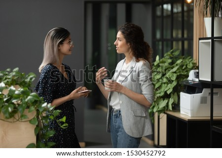 Asian and Caucasian ethnicity businesswoman talking discuss common project standing in workplace hall more experienced employee share knowledge with intern during coffee break in modern office hallway