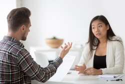 Asian and caucasian partners negotiating on contract terms at meeting, chinese businesswoman disagreeing arguing with businessmen having claim complaint about fraud scam, dispute about terms concept
