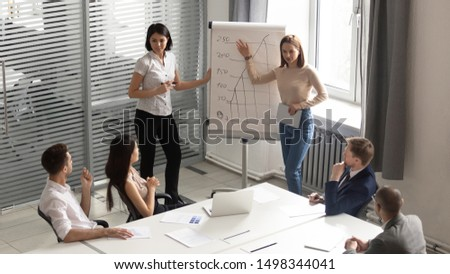 Asian and caucasian professional female business trainers or coaches giving flip chart presentation, explaining graphs to mixed race concentrated employees at modern boardroom, top overhead view.