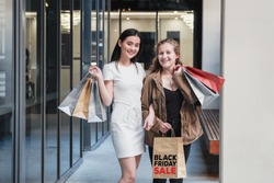 Asian and caucasion mixed race young women carrying shopping bags, Black friday sale concept