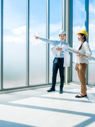 Asian architect Male and female inspecting construction work inside high-rise building near huge window glass on blue sky background. Couple engineer in hard hats holding blueprint in new building.